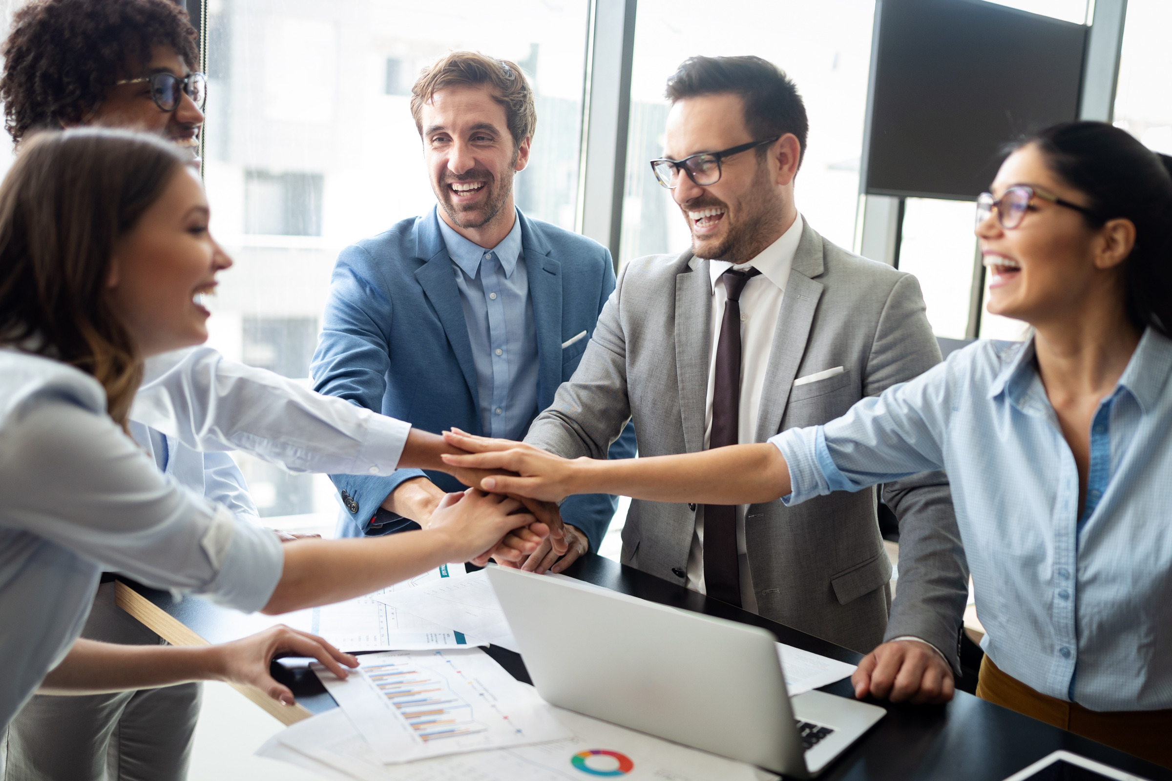 business group of people putting hands together in circle